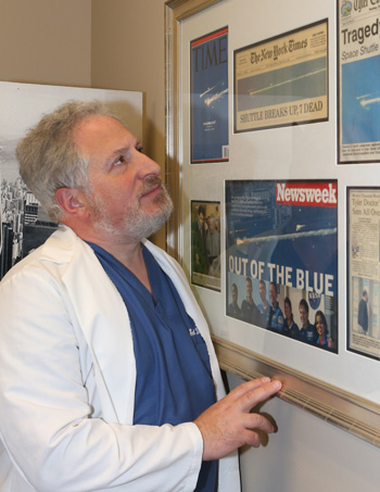 Dr. Lieberman in scrubs looks at the newspapers and magazines displayed on the wall.