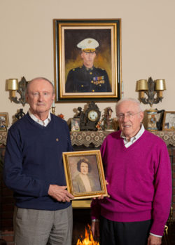 Two men hold a picture, standing in front of a fireplace, with their brother's portrait over the mantle.