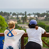 Two students lean on a railing, looking out over the landscape and toward the ocean in Ghana.