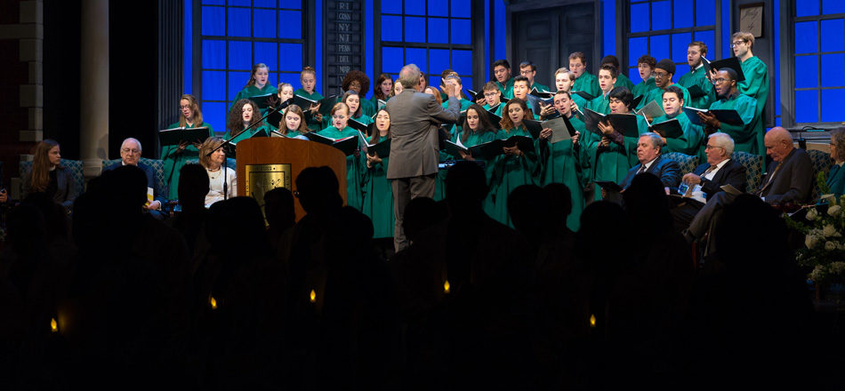 The Wagner Choir sings on stage as students in front hold candles.