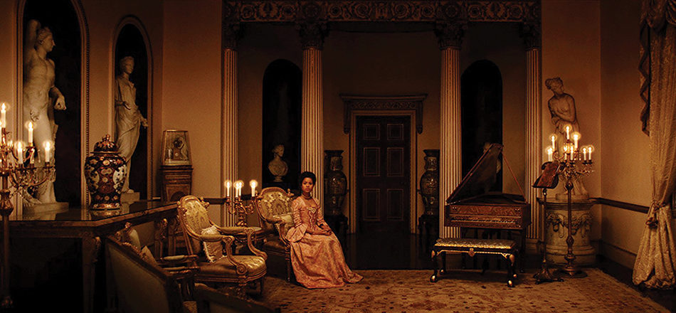 A lone black woman in a beautiful gown sits in an ornate room.