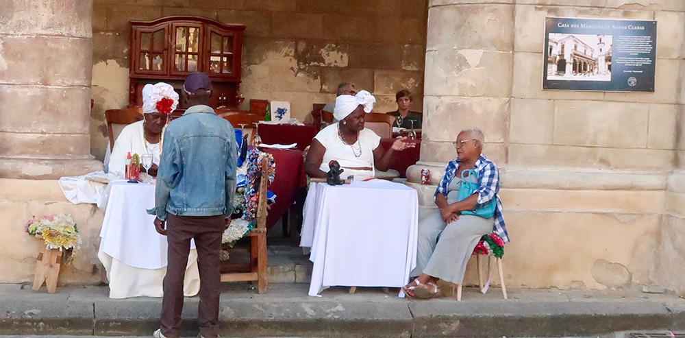 Two women dressed in white and with white headwraps sit at tables on a sidewalk, talking to people.